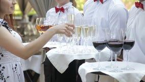Os gar?ons cumprimentam convidados com bebidas alco?licas Champagne, vermelho, vinho branco em bandejas video estoque