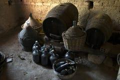Os garrafões velhos envelheceram garrafas de vinho e tambores de madeira em um porão Foto de Stock Royalty Free