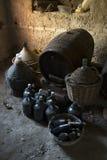 Os garrafões velhos envelheceram garrafas de vinho e tambores de madeira em um porão Fotos de Stock Royalty Free