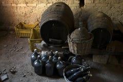 Os garrafões velhos envelheceram garrafas de vinho e tambores de madeira em um porão Fotografia de Stock Royalty Free