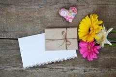 Os Gerberas florescem com dois corações, envelope e Livro Branco na madeira Imagens de Stock Royalty Free