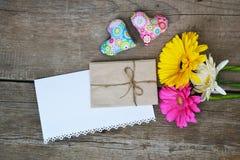 Os Gerberas florescem com dois corações, envelope e Livro Branco na madeira Imagens de Stock