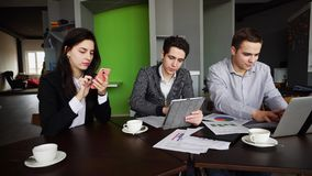 Os gerentes concentrados, dois indivíduos e a menina são contratados ativamente dentro Fotos de Stock