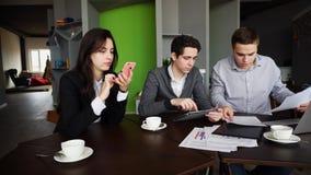 Os gerentes concentrados, dois indivíduos e a menina são contratados ativamente dentro Imagens de Stock