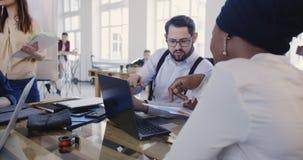 Os gerentes de empresa de mercado multi-étnicos trabalham junto com diagramas e portátil na tabela do escritório do sótão Local d vídeos de arquivo