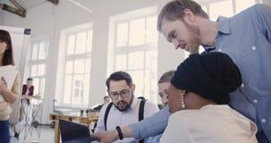Os gerentes de empresa de mercado profissionais multi-étnicos cooperam sobre o portátil na tabela moderna do escritório do sótão, filme