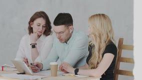 Os gerentes de vendas discutem o impacto das novas tecnologias no mercado usando a tabuleta As negociações principais do gerent vídeos de arquivo