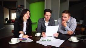 Os gerentes, a mulher e os homens ativos e engraçados falam sobre o trabalho e estudam papéis importantes, sentam-se na tabela co video estoque