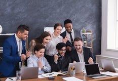 Os gerentes multirraciais felizes terminaram com sucesso o projeto duro fotografia de stock royalty free
