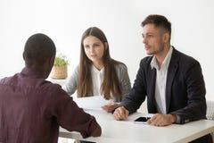 Os gerentes sérios da hora escutam o candidato africano na entrevista de trabalho Foto de Stock Royalty Free