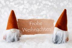 Os gnomos de bronze com cartão, texto Frohe Weihnachten significam o Feliz Natal Fotografia de Stock