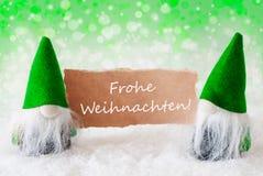 Os gnomos naturais verdes com cartão, Frohe Weihnachten significam o Feliz Natal foto de stock