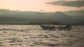 Os golfinhos que saltam na frente do barco com 3 povos vídeos de arquivo
