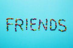 Os grânulos coloridos das crianças, dispersados em um fundo azul, a palavra foto de stock