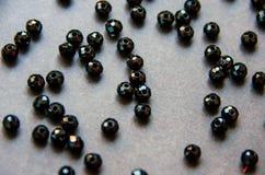 Os grânulos coloridos, pretos e as pedras isolaram o fundo cinzento fotografia de stock