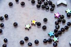 Os grânulos coloridos, pretos e as pedras isolaram o fundo cinzento imagem de stock