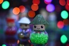 Os grânulos de vidro no frasco de vidro no bokeh colorido borraram o fundo O ` s do Natal e do ano novo brinca sobre no fundo col Foto de Stock Royalty Free