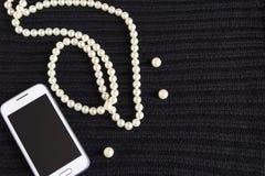 Os grânulos e o telefone do ` s das mulheres no preto fizeram malha a tela Imagens de Stock Royalty Free