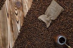 Os grãos de café pretos são dispersados de um saco de linho em uma tabela de madeira fotografia de stock