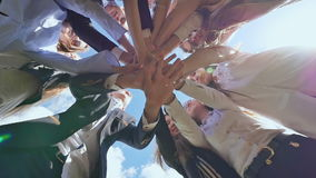 Os graduados amigáveis da escola superior põem suas mãos sobre se e abrem-nas contra o céu azul Luz do dia ensolarada vídeos de arquivo