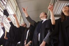 Os graduados nos vestidos que jogam seu almofariz embarcam no ar imagem de stock