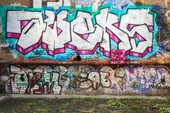 Os grafittis abstratos coloridos text testes padrões na parede de tijolo Fotos de Stock