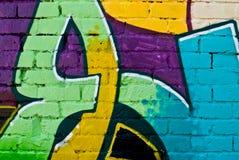 Os grafittis detalham em uma parede de tijolo textured Imagens de Stock Royalty Free