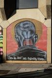 Os grafittis em uma parede que mostra um ` s do homem dirigem Imagens de Stock