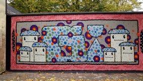 Os grafittis muram com caras Fotografia de Stock