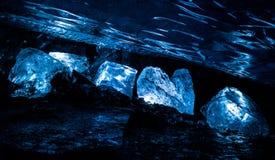 Os grandes blocos de gelo iluminaram-se acima dentro de uma caverna de gelo profundamente dentro do Spenc imagem de stock