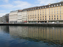 Os grandes hotéis dão forma a reflexões no rio de Rhone Fotografia de Stock Royalty Free