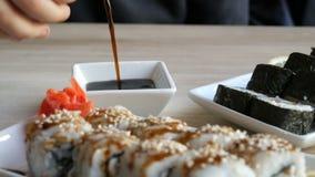 Os grandes rolos de sushi brancos e pretos bonitos saborosos da culinária japonesa estão na bandeja na tabela no restaurante filme