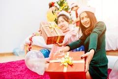Os grupos de amigos são homens asiáticos e as mulheres decoraram a árvore de Natal fotografia de stock