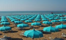 Os guarda-chuvas azuis alinharam em uma praia norte do mar de adriático Foto de Stock Royalty Free