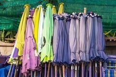 Os guarda-chuvas de praia fecharam-se colocado junto contra a parede tailândia imagem de stock