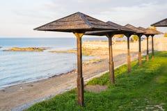 Os guarda-chuvas decorativos feitos da palma ramificam no fundo da praia Foto de Stock Royalty Free