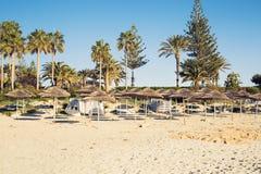 Os guarda-chuvas decorativos feitos da palma ramificam no fundo da praia Fotografia de Stock Royalty Free