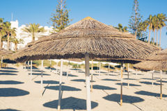 Os guarda-chuvas decorativos feitos da palma ramificam no fundo da praia Foto de Stock