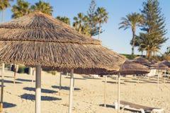Os guarda-chuvas decorativos feitos da palma ramificam no fundo da praia Imagens de Stock Royalty Free