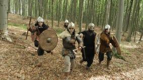 Os guerreiros de Viquingues estão correndo na floresta na batalha video estoque