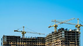 Os guindastes e os trabalhadores de construção do lapso de tempo constroem uma construção do multi-andar imagem de stock