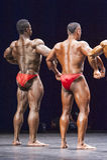 Os halterofilistas mostram ao seu a pose traseira na fase Imagens de Stock