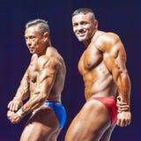 Os halterofilistas mostram seu físico na fase no campeonato Fotos de Stock Royalty Free