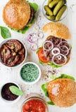 Os hamburgueres caseiros com cebola, salmouras da carne, vegetais, sol-secaram tomates, especiarias imagens de stock royalty free