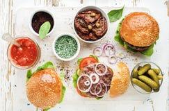 Os hamburgueres caseiros com cebola, salmouras da carne, vegetais, sol-secaram tomates, molho fotografia de stock
