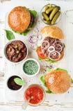 Os hamburgueres caseiros com cebola, salmouras da carne, vegetais, sol-secaram tomates, molho imagens de stock