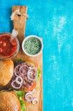 Os hamburgueres caseiros com cebola, vegetais da carne, sol-secaram tomates Copie o espaço fotos de stock