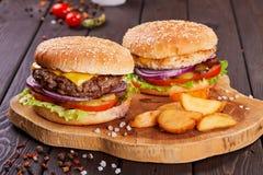Os hamburgueres saborosos da carne fresca com salada e queijo serviram na placa de madeira fotografia de stock royalty free