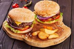 Os hamburgueres saborosos da carne fresca com salada e queijo serviram na placa de madeira foto de stock royalty free