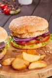 Os hamburgueres saborosos da carne fresca com salada e queijo serviram na placa de madeira fotos de stock royalty free